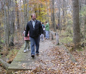 Ann Arbor Public Schools Environmental Consultant Dave Szczygiel leads Lakewood Elementary fourth-graders across a bridge at Waterloo as they look for signs of decomposition in the woods.