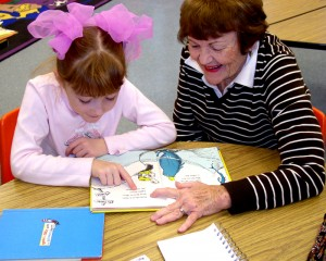 Rotarian Jeannine Buchanan works with a young student reading at Angell Elementary School. The Rotary Club of Ann Arbor has had a partnership with the school district for 12 years. For more, scroll down to the story below.