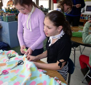 Students work together as a team to create colorful blankets for the needy.