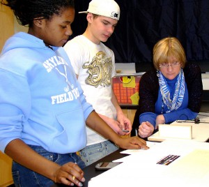 Science teacher Kathe Blue Hetter works with students in a physics lab.