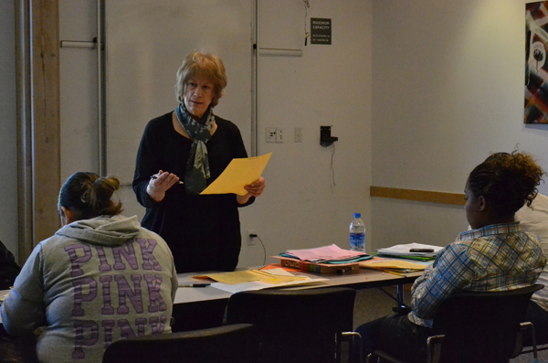Beth Carlson helps students through math exercises during a GED prep class last fall.