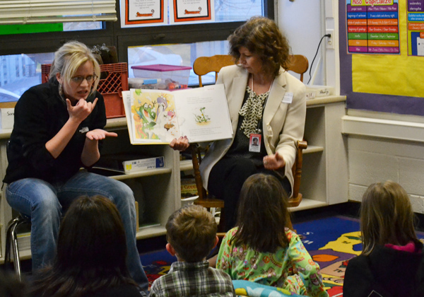 Lauren Leese signs as Assistant Superintendent of Elementary Education Dawn Linden reads to a group of students.