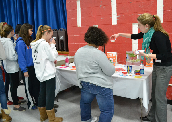 Courtney Boes, a health educator with Project Healthy Schools, shows students how much sugar is in their favorite beverages.