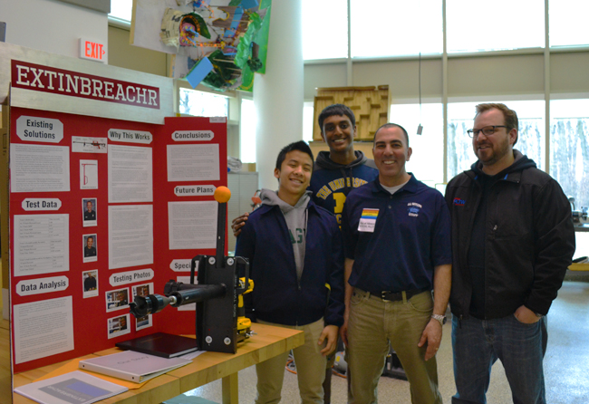 Skyline students Albert Foo and Sharath Anand show off the prototype ExtinBreachR with Design, Technology and Environmental Planning teacher Tom Pachera and student teacher Frank Norton.