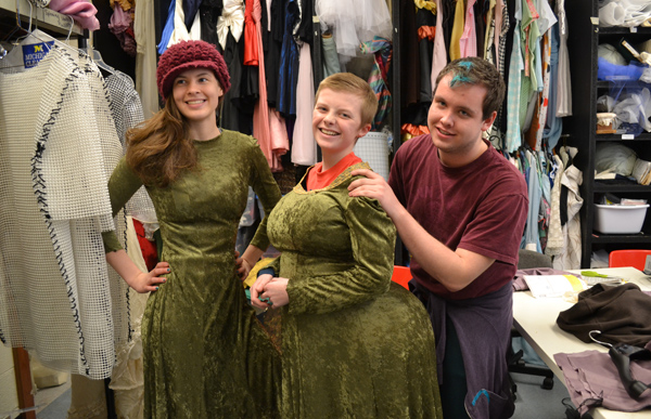 Chelsea Stauffer, Joe Riesterer and Mitch Fehrle show off two of Princess Fiona's dresses that the costuming students created. Fiona undergoes many physical transformations in the show, necessitating dresses of different sizes and a fat suit.