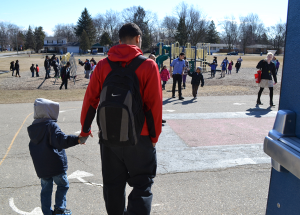 "The Rising Scholars program provides many volunteer opportunities. Here a Huron scholar holds the hand of his Carpenter Elementary ""buddy."" The two spent time reading together and playing outside. Called the ""Carpenter Project,"" it provides scholars time to mentor kindergarteners."