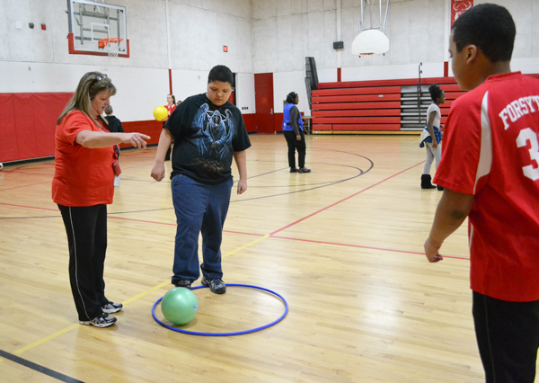 Gym teacher Kelly Bert and a seventh grade peer mentor help a special needs student during the adaptive gym class at Forsythe Middle School.