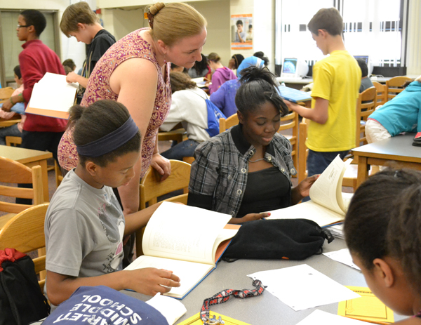 English Language Arts teacher Ellen Daniel checks out the volume with students.