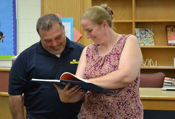 Scarlett Principal Gerald Vazquez and teacher Ellen Daniel smile over the seventh-graders' book.