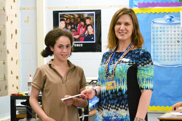 Meals on Wheels Director Beth Adams accepts a $525 donation from Tahani Othman's fifth grade class Tuesday, June 11.