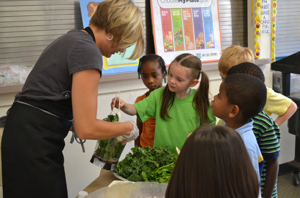 Chartwells Director Heather Holland lets students pick ingredients during a smoothie-making demonstration at the Summer Learning Institute July 25, 2013.