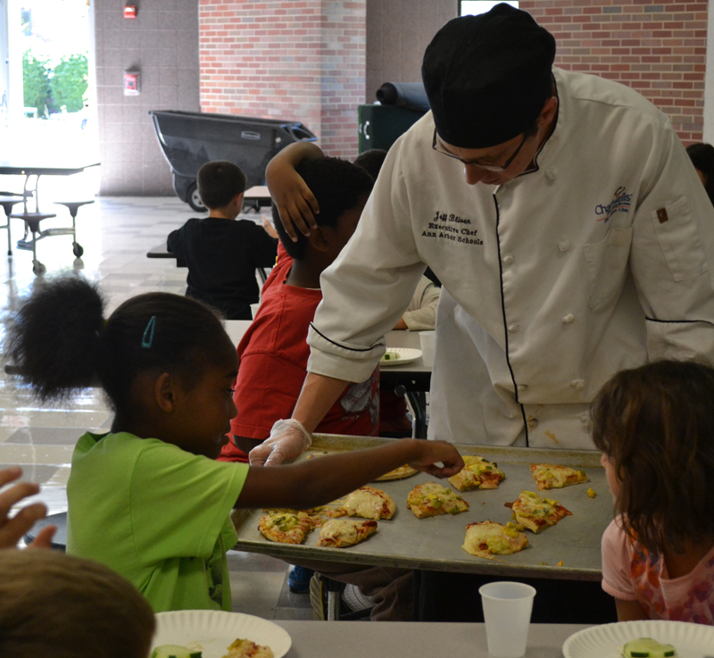 Chartwells Executive Chef Jeff Bliven passes out fresh-from-the-oven pizzas that the campers made.