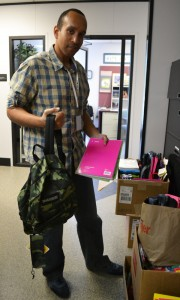 Azibo Stevens helps connect homeless students and their families with needed services, such as this donation of backpacks and supplies from ADP.