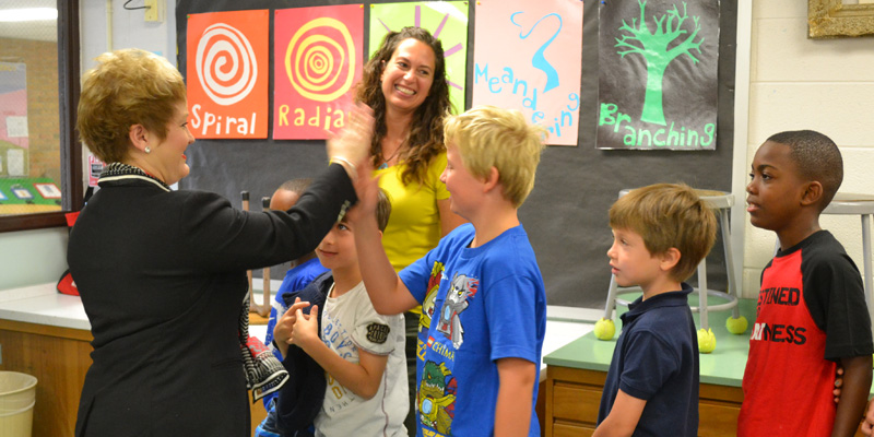 Dr. Swift high fives a Thurston student as he leaves Amanda Wyse's art class.