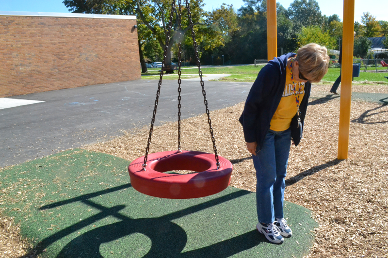 Monkiewicz stands on the pored rubber surfacing that allows a wheelchair or a walker to roll up to the swing.