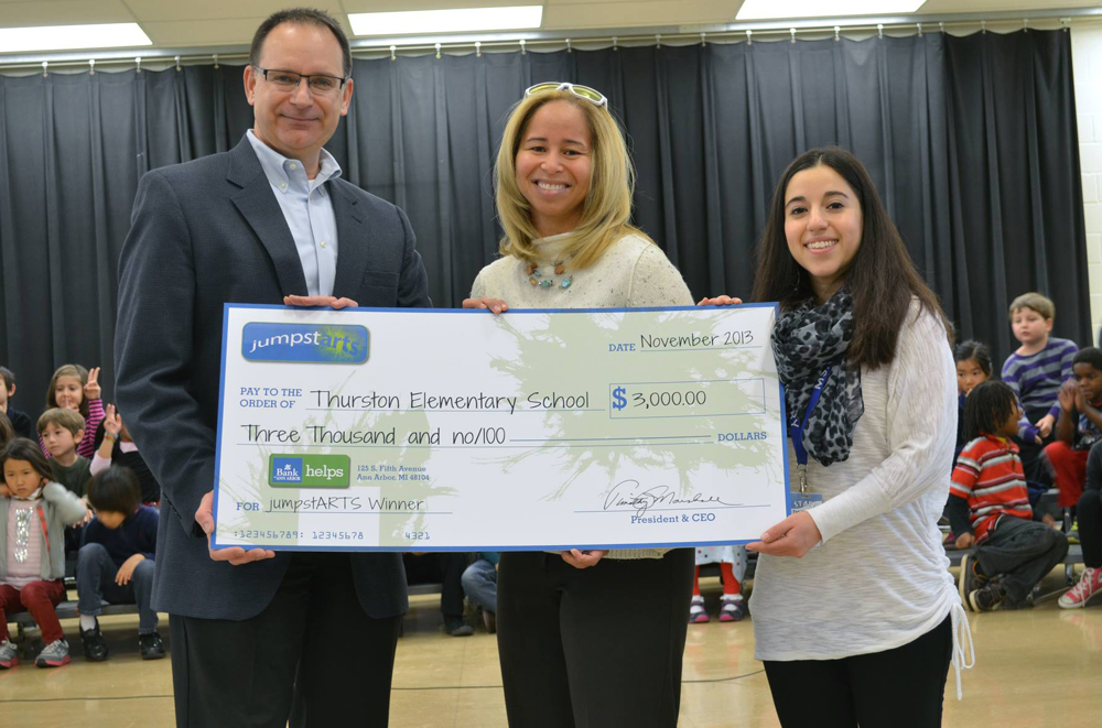 Thurston Principal Natasha York accepts the donation from Michael Cole. Photo provided by Bank of Ann Arbor.