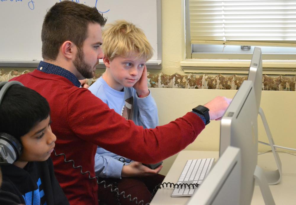 Google employee Eldridge Alexander helps a student work through a game offered on code.org.
