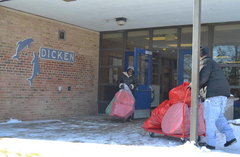 Custodians Jennifer Mason and Rick Redding distribute gifts at Dicken Elementary Monday, Dec. 16.