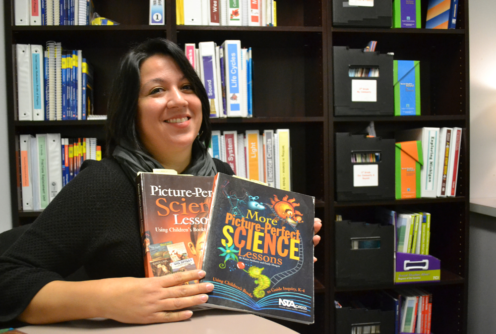 K-5 Curriculum Coordinator Rose Marie Callahan holds two Picture Perfect Science books. Each has 14 lessons and comes with 28 fiction and nonfiction books to give science lessons context. Each school will get one set (a total of 29 books), which can be used by many teachers across multiple grades.