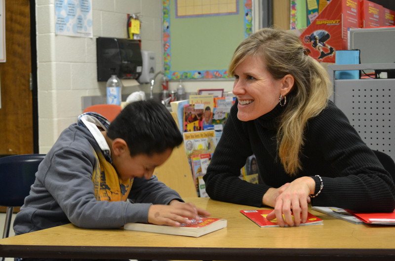 A volunteer tutor laughs with an Allen Elementary student in this December 2012 file photo.