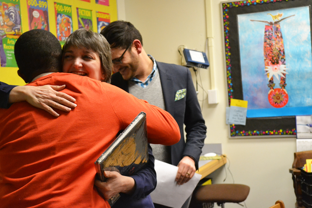 Kristi Bishop hugs Omari Rush after learning she was named Teacher of the Year by the University Musical Society and the DTE Energy Foundation.