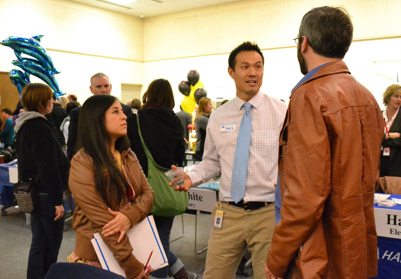 Bach Elementary Principal Hyeuo Park and Eberwhite Principal Bill Harris talk with parents at the district's first Schools of Choice Open House on March 11, 2014.