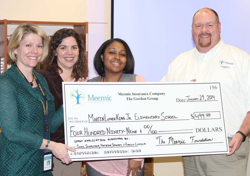 Gordon Group Agency Vice President Bill Christensen presents a check to excited teachers at King Elementary.