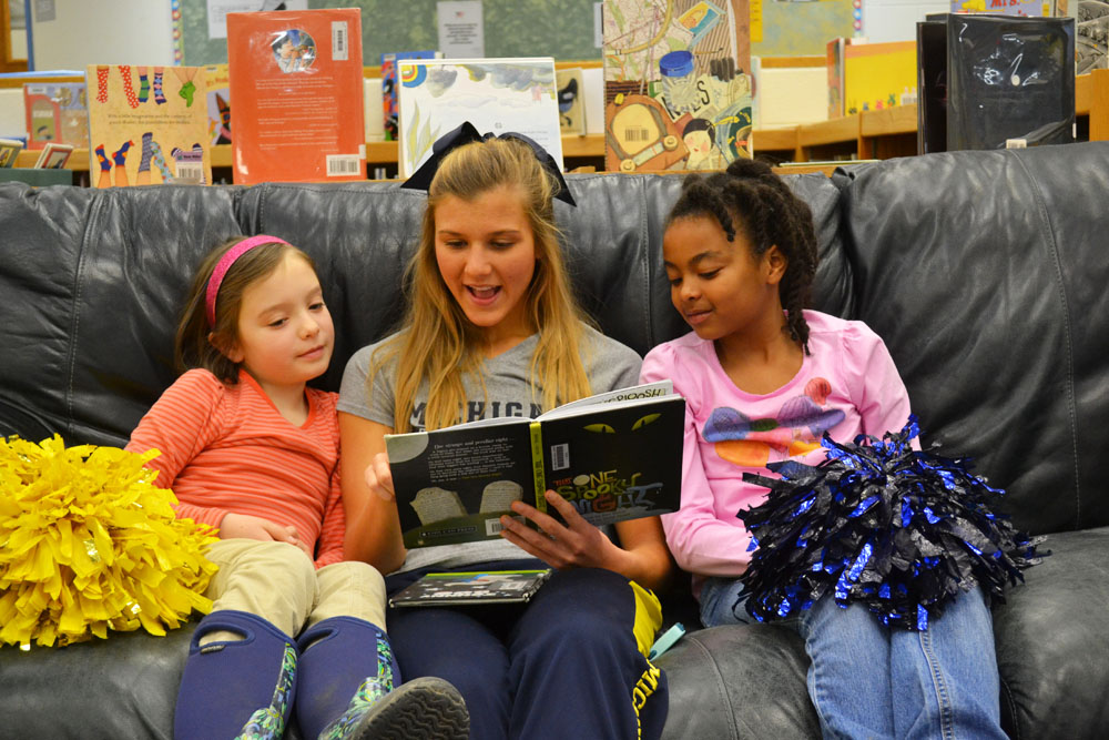 U-M cheerleader Jessica Wadel reads to Ann Arbor Open students on March 21, 2014.