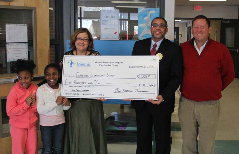Gordon Group Agency President Stew Gordon presents a check to Carpenter Interim Principal Ed Broom and teacher Ann Borders.