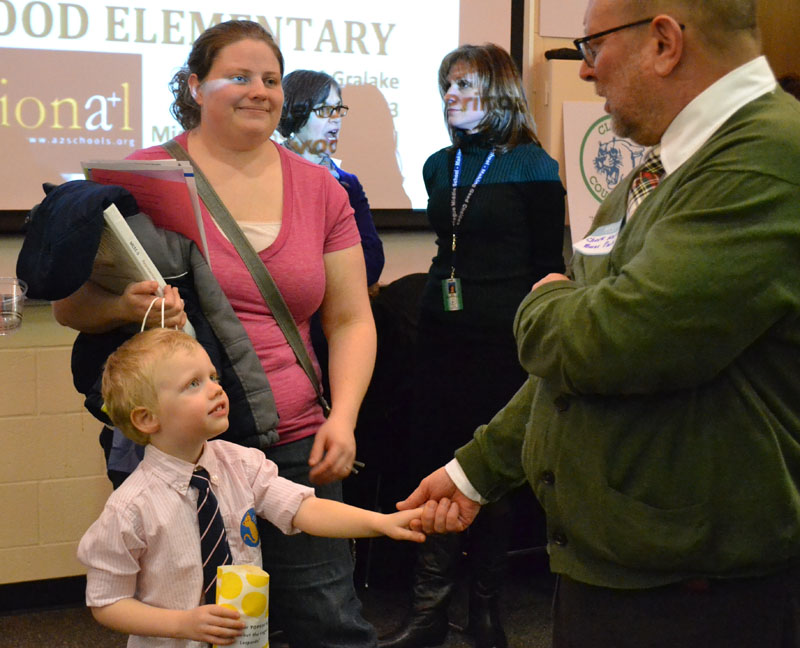 Lea Oom smiles as her four-year-old shakes hands with Burns Park Principal Chuck Hatt.