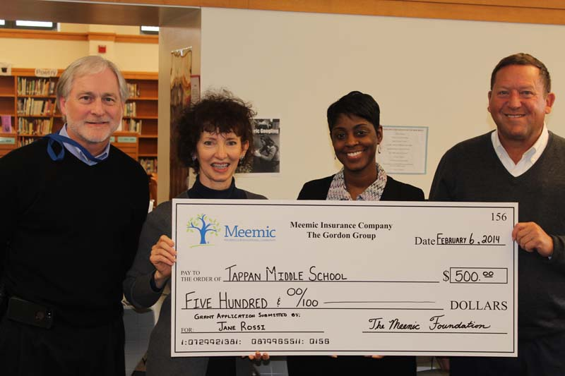 Stew Gordon a donation check to Tappan Middle School.