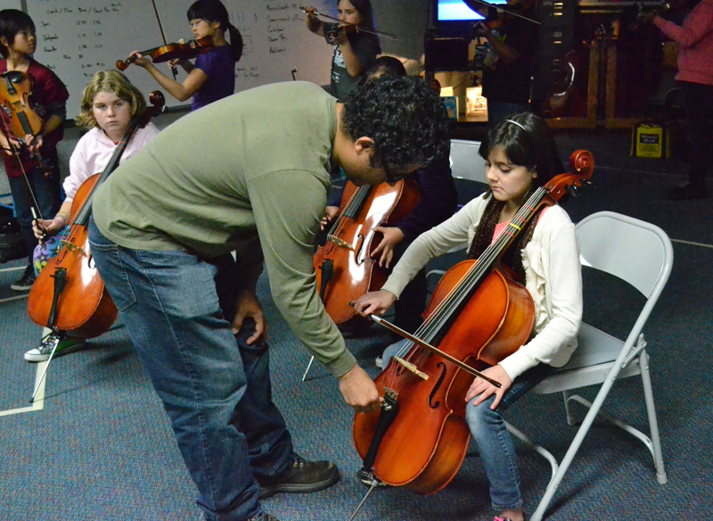 Horacio Contreras, who learned to play cello in the El Sistema in Venezuela, gives a Mitchell fifth grader individual attention during class.