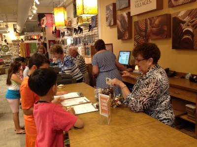 Ten Thousand Villages volunteers assist 4th graders to learn the stories of the people who produced the fair trade products in the store.