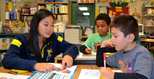 Golfer Kathy Lim helps students with a project.