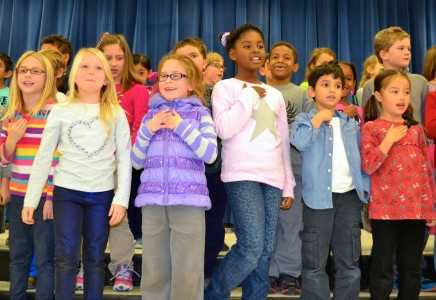Second graders sing during the assembly.
