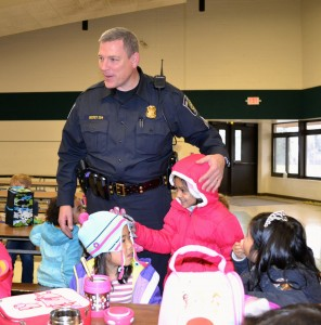 Hickey, shown visiting students in the cafeteria, says it's important for children to get to know police officers and other community helpers.