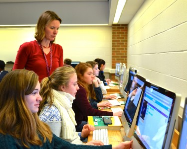 Huron media specialist Jennifer Colby looks on as students go through the coding tutorials during Hour of Code.