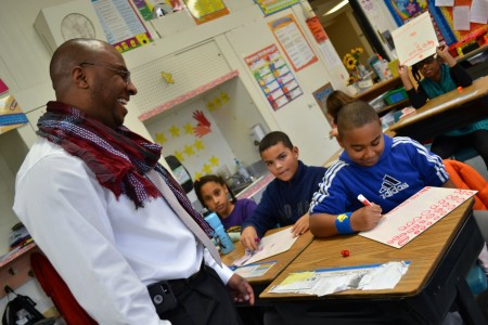 Johnson checks on his son, Kellen, a fourth grader in LaKeisha Drummer's class.