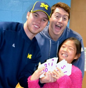 Ann Arbor native Travis Maezes and teammate Evan Hill congratulate fourth grader Rachel Wei, a math lover, for winning a round of flash cards.