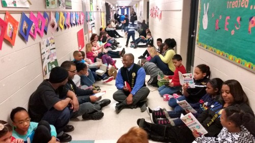 "At Carpenter Elementary, parents, staff and community volunteers read to the students throughout the school during ""Stop Drop and Read"" hour. Principal Michael Johnson is photographed in the middle of the hallway, with his own father and son, who volunteered today."