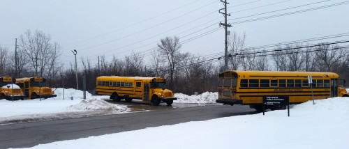 Drivers leave the AAPS transportation lot to pick up students after school.
