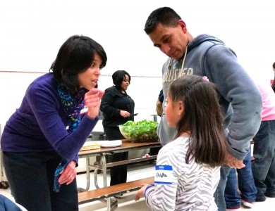 teacher   talks to parent Juan Carlos and his daughter, Alondra, who is her student