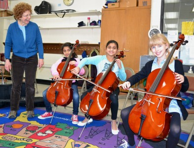 AAPS instrumental music teacher Rosalie Koenig, with three young cellists at Bach Elementary.