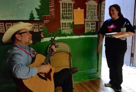 "Sandy Kreger joins Principal Chuck Hatt (aka ""Cowboy Bob"" in a round of ""Hey, Mr. Tambourine Man"" at the blood drive."