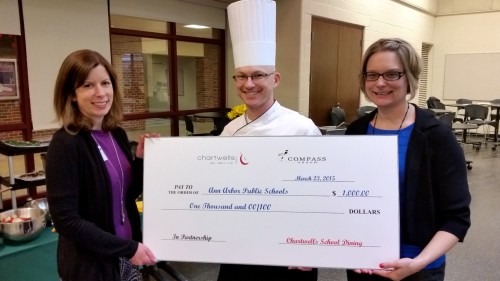 Jenna Bacolor accepts a check from Chartwells chef Shawn Lenhardt and food service director Heather Holland.