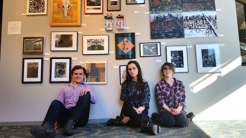 Alex    , Ada Banks and Erika Chesky sit in front of their artwork and that of 10 fellow Community High School students on display at WSG Gallery.