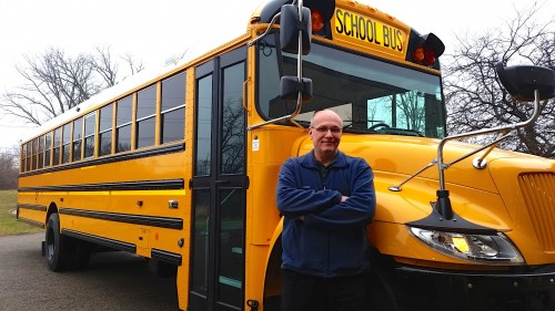 John Nikolich stands by a bus on loan to the district that is similar to one it would purchase if the bond is renewed.