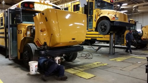 Maintenance workers Darren Cline and John Maxwell work on AAPS school busses.