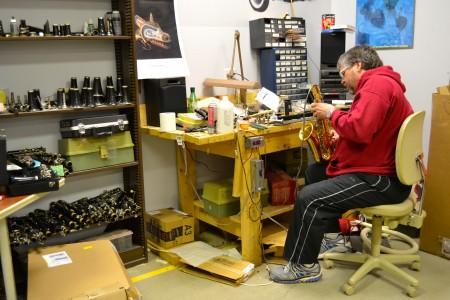 Band teacher Doug Horn repairs a saxophone in the Balas warehouse.