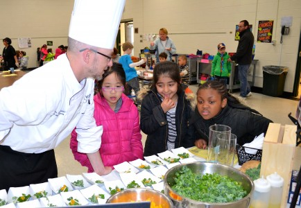 Chef     tries to interest some doubtful elementary students into trying the Jicama Kale Salad.
